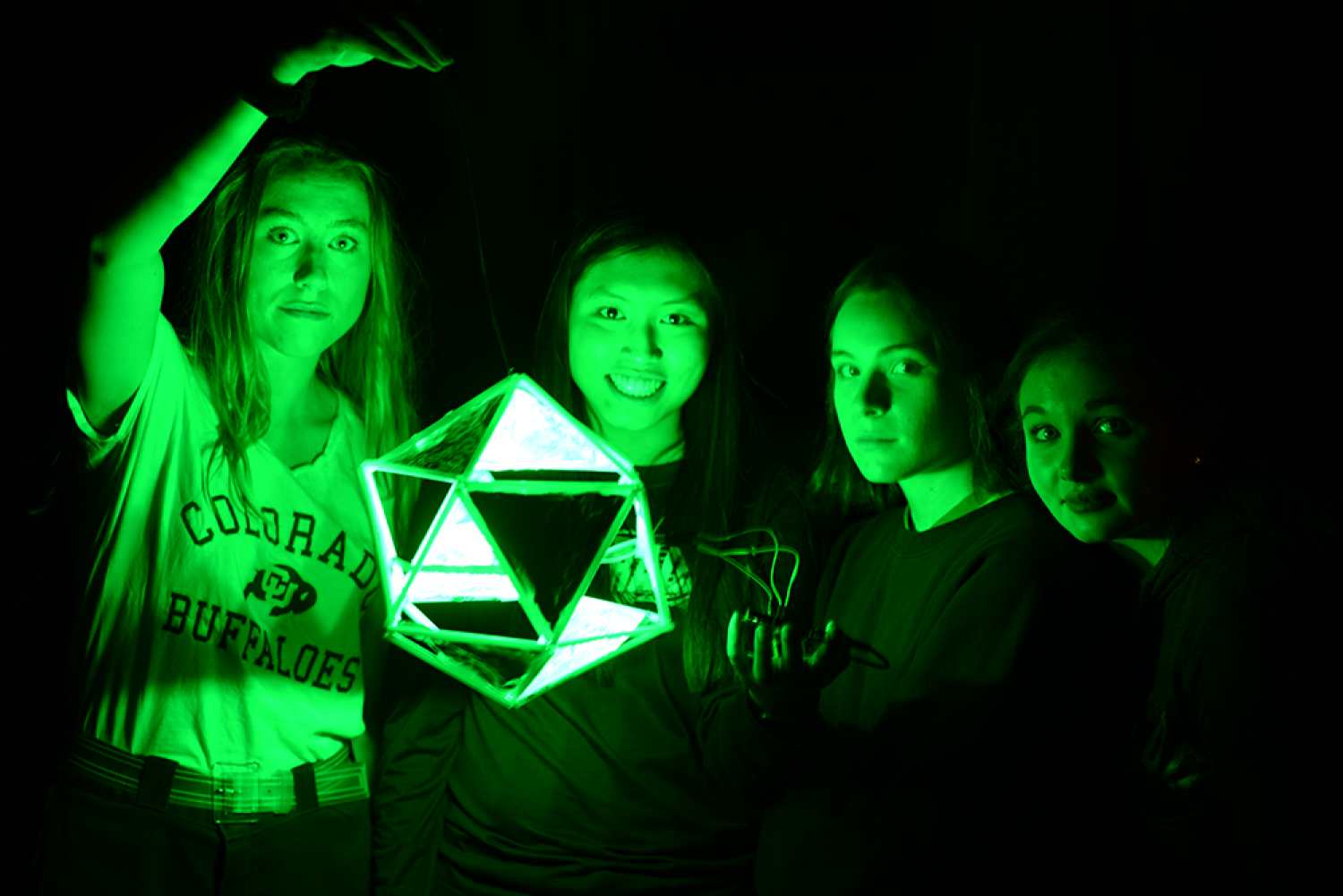 """Kylie McKee, Rylee Gordon, Ashley Koett & Rebecca Geist are lit by the green glow of one of the sample lights for their project, """"Tunnel VIsion."""""""