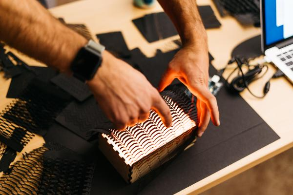 Laser cut black paper pattern over lit-up box