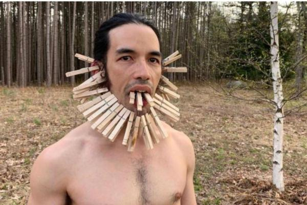 man with clothes pins framing face and attached to tongue