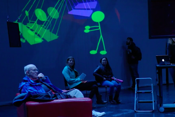 """Photo of people in front of screen at """"Resonant"""""""