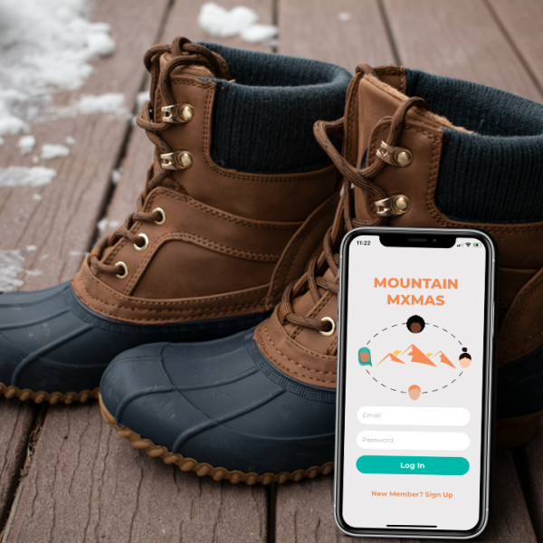 Hiking boots with a cell phone leaning on it which shows the Mountain Mxmas app.