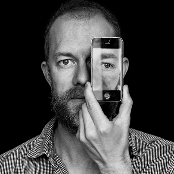 Kevin Hoth holds a phone displaying a photo of his eye in front of his left eye.