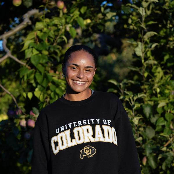 India Johnson in a CU sweatshirt in front of some tree branches.