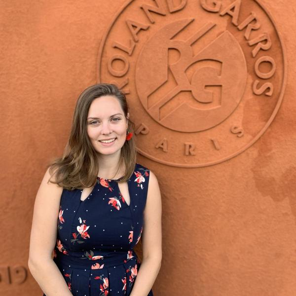 Jessie Hamilton in front of a wall that says Roland Garros Paris.