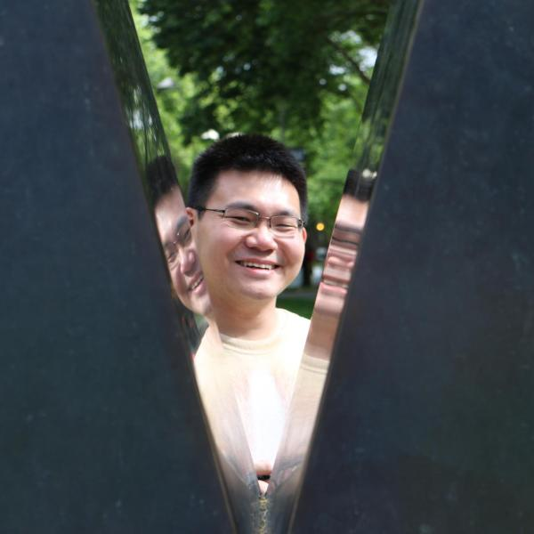 """Jiaji Sun stands behind a V-shaped sculptured that shows his reflection on each side of the """"V."""""""