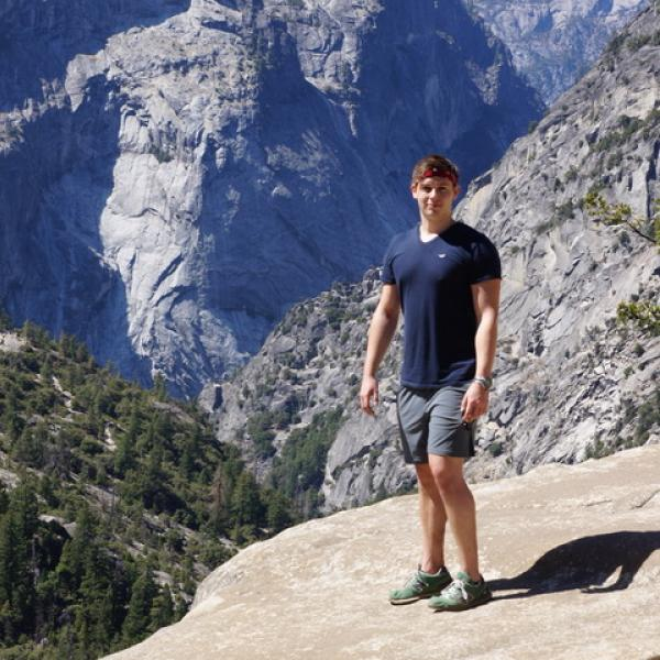 Lukas Buecherl stands on a rock in front of mountain scenery.