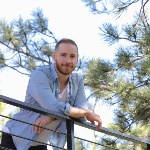 Ryan Dennie looking down from a deck with pine trees.