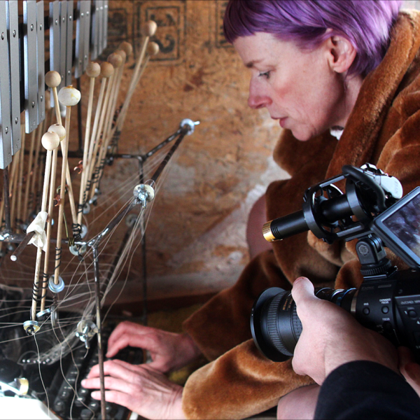 Michelle Ellsworth with purple hair types at an old-style typewriter with a contraption of wood, string and metal  coming out of it while someone out of the shot points a camera at her.
