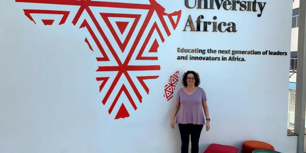 Aileen Pierce stands in front of a CMU Africa sign
