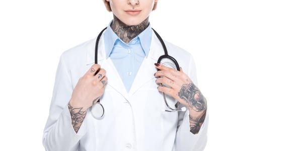 Photo of tattoos person in lab coat with stethoscope
