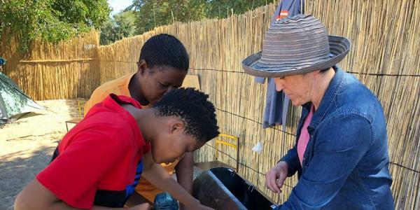 Kari Santos teaches two women to make the peanut roaster.