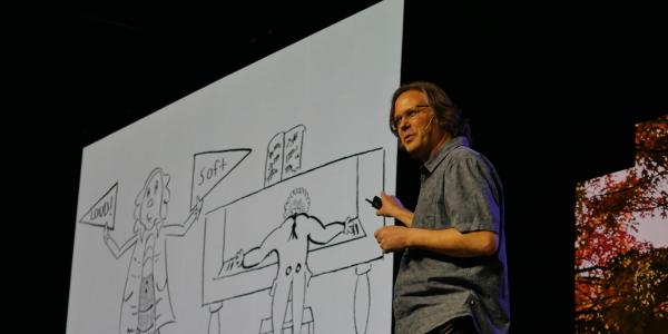 Michael Theodore points to a large cartoon drawing that he drew of a man at a piano and another man holding loud and soft signs.