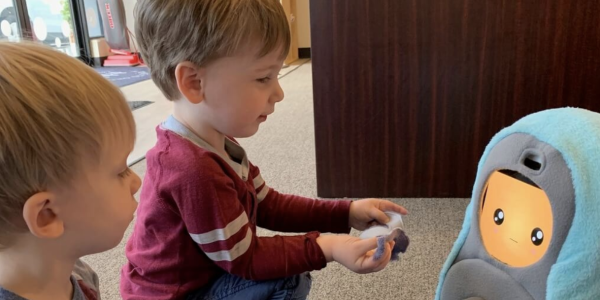 Two young boys engage with the PEERbots app.
