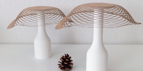 Two Sensing Kirigami lampshades sit on a table with a pine cone between them.