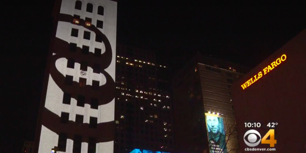 Screenshot of CBS video featuring @ sign projection on building