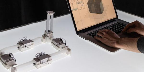 Photo of ShapeBots next to laptop
