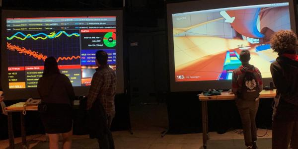 Participants at the Whaaat!?Festival playing videogames on large screens.