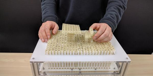 Dynablock constructs a miniature 3D model by assembling 3,000 9 mm blocks, leveraging a 24 x 16 pin-based shape display as a parallel assembler.