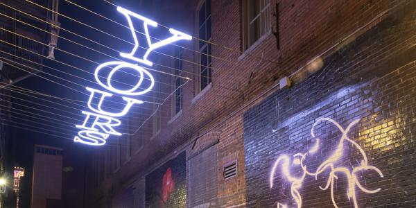 """The light-based installation, """"Y/OURS,"""" hangs above a Denver Alley."""