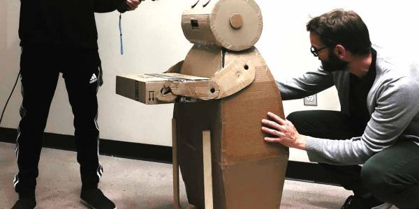 Daniel Leithinger and student working with vr headset and cardboard robot