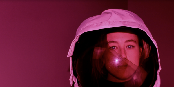 Woman in a helmet that looks like a space helmet with a red tinge to the image.