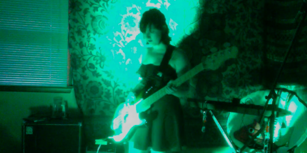 Annie Kelly playing bass and controlling a light show in real-time using cardboard foot pedals to trigger different lighting effects that she programmed ahead of time.