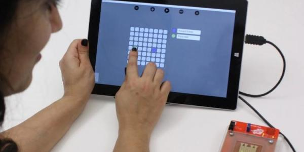 Person using a tablet to control droplets on the OpenDrop biochip.