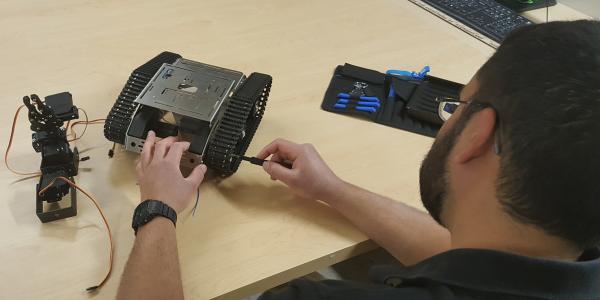 Photo of a man fixing robot