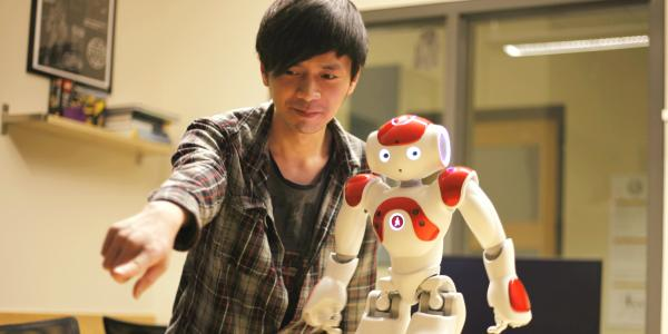 Bryan Bo Cao interacts with a small robot