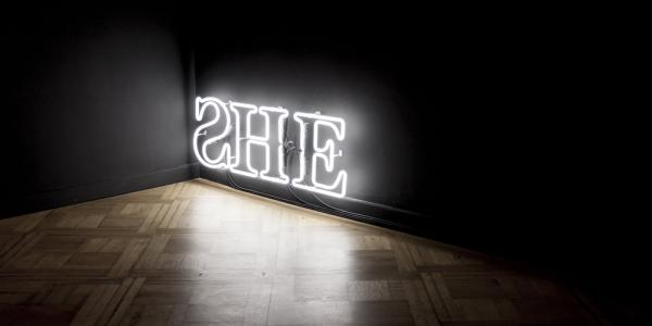 """Neon sign that spells """"SHE"""""""
