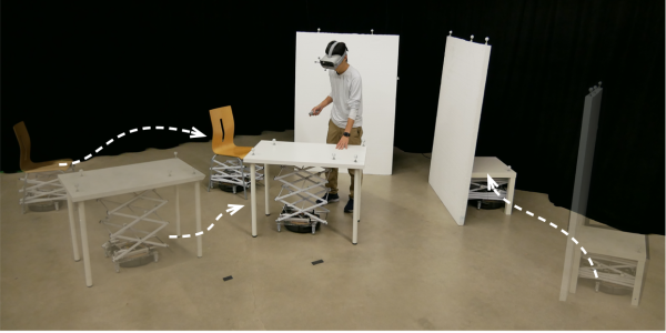 Person with VR goggles touches a table that has a Roomba with a mechanical scissor lift below.