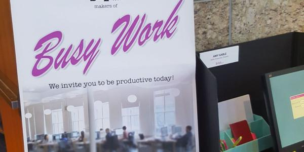 "Sign posted in an office. It says, ""Busy Work. We invite you to be productive today."""