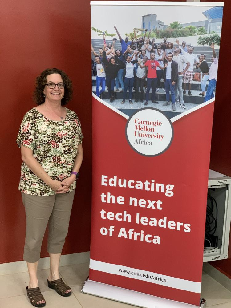 """Aileen Pierce standing next to a sign that reads """"educating the next tech leaders of Africa."""""""