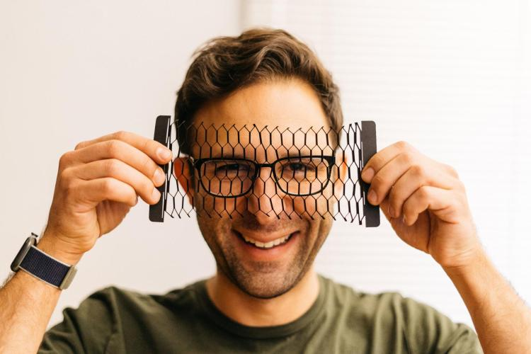 Bryan holds diamond-patterned laser-cut carbon-coated paper in front of his face.