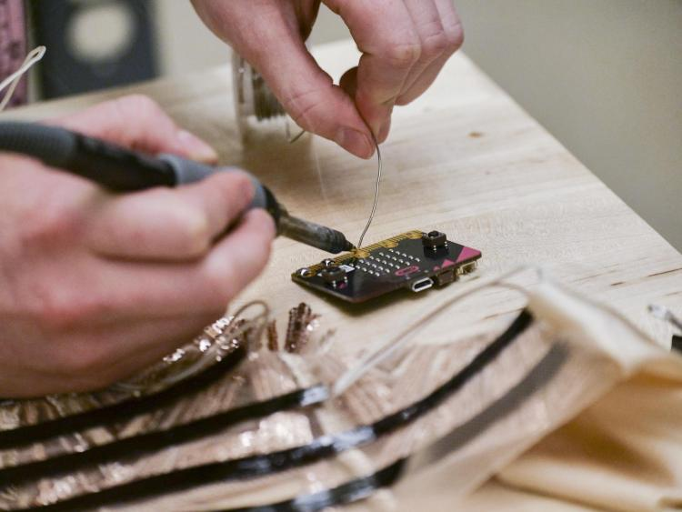 Close up of Emily Daub using a soldering iron as she works in her lab in the Atlas building on the CU Boulder campus.