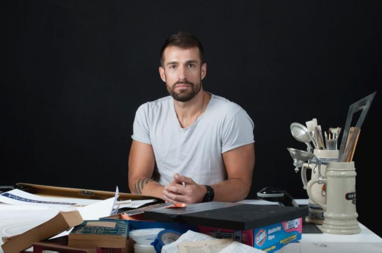 Joel Swanson in a white T-shirt sits behind his desk covered with art supplies.