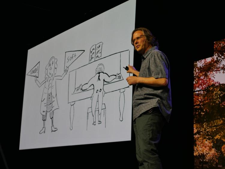 Michael Theodore points to a large cartoon drawing that he drew of a