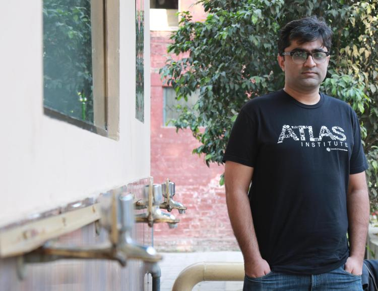 Mustafa Naseem stands with a black ATLAS shirt next to water nozzles in Pakistan.