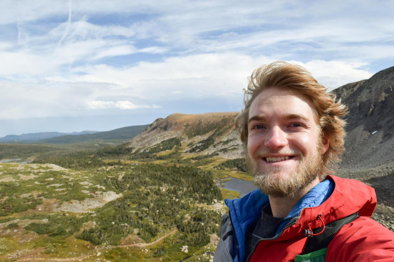 Nate Bennett in a jacket in front of a wide expanse of mountains and sky.