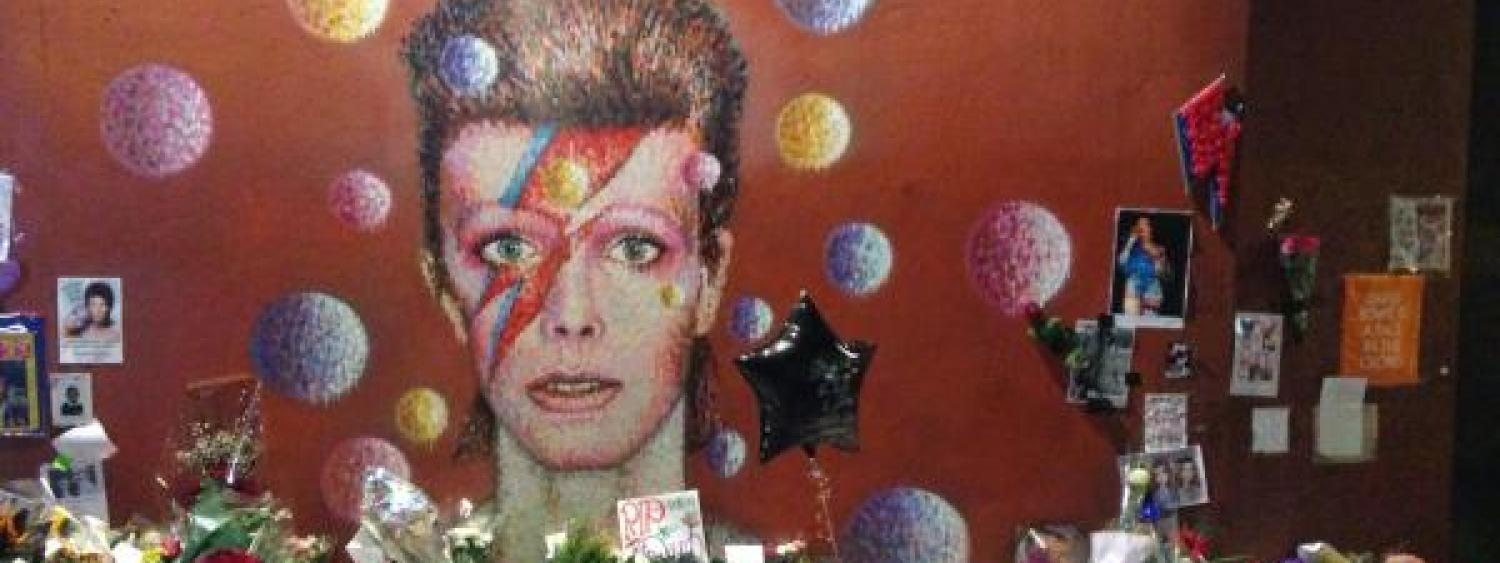 David Bowie's face painted on a wall with flowers in front of it from grieving fans.
