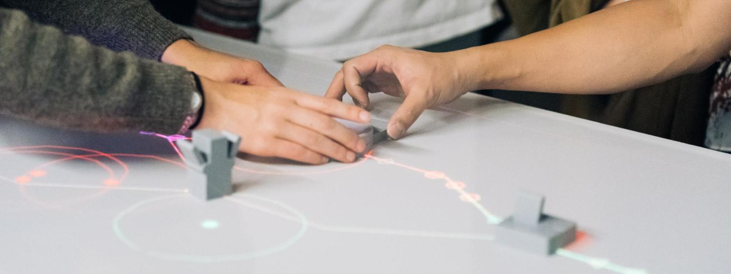 People touching 3D printed controller sitting on a table with projections
