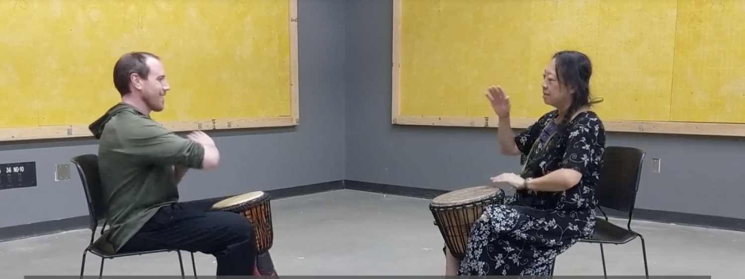 Ellen Do and Torin Hopkins face each other while playing Djembe drums.