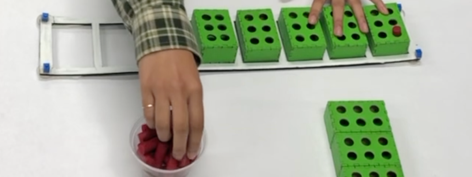 A BrailleBlocks user building a word with the blocks and pegs. There is a white frame on the table with rectangle slots. There are 8 slots in a row. 5 of the slots have green blocks in them which resemble Braille cells. The user is reaching for red pegs which she is placing in the block holes to create Braille letters.