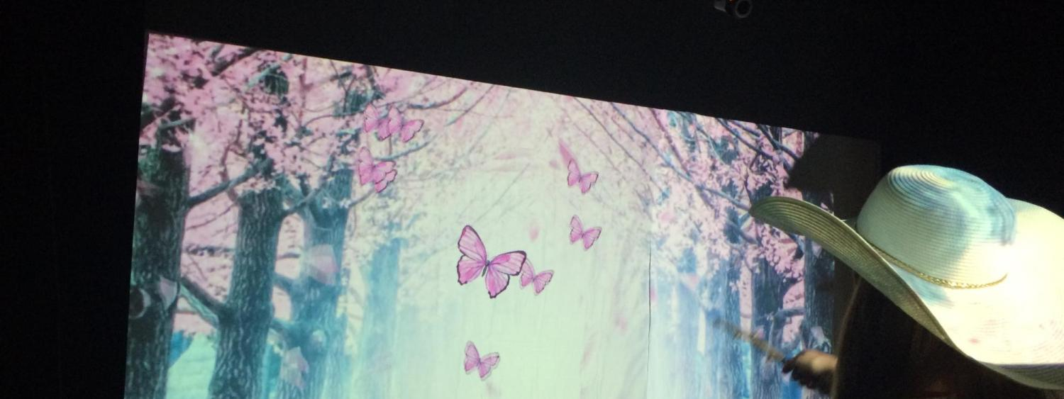 projected image of butterflies following the movement of a tree branch in a woman's hand
