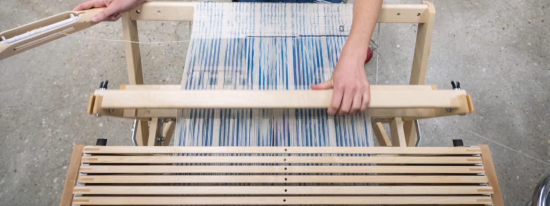 Laura Devendorf weaving at a loom.