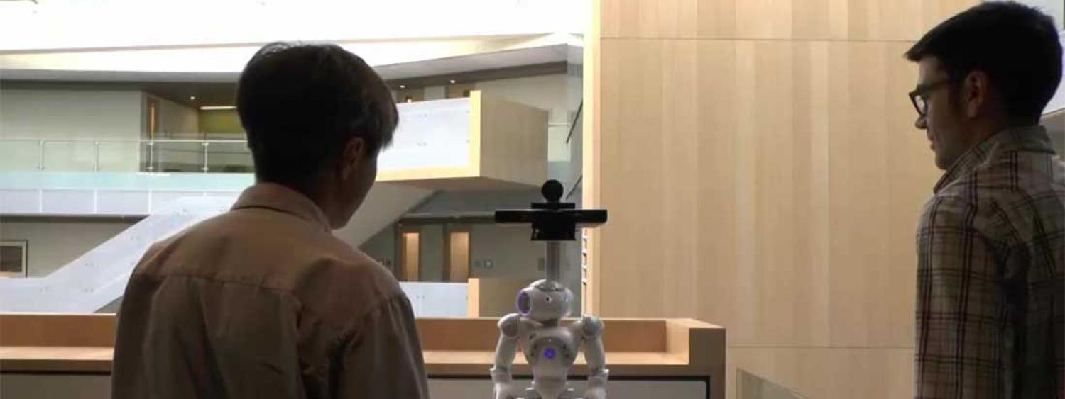 Two people look at a robot.