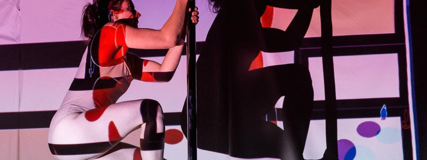 Woman pole dancing in front of interactive projections