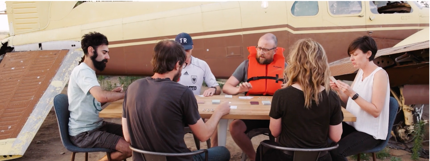 Wearing a life preserver, game creator Danny Rankin sits at a table with other players in front of an old beat up plane.