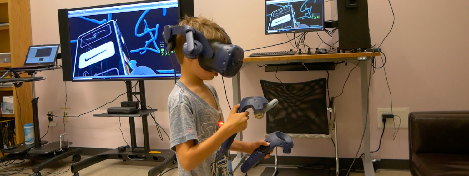 Photo of young boy using VR headset to draw
