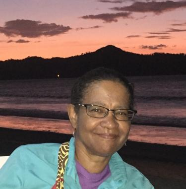 Donna Auguste in front of an orange sunset.